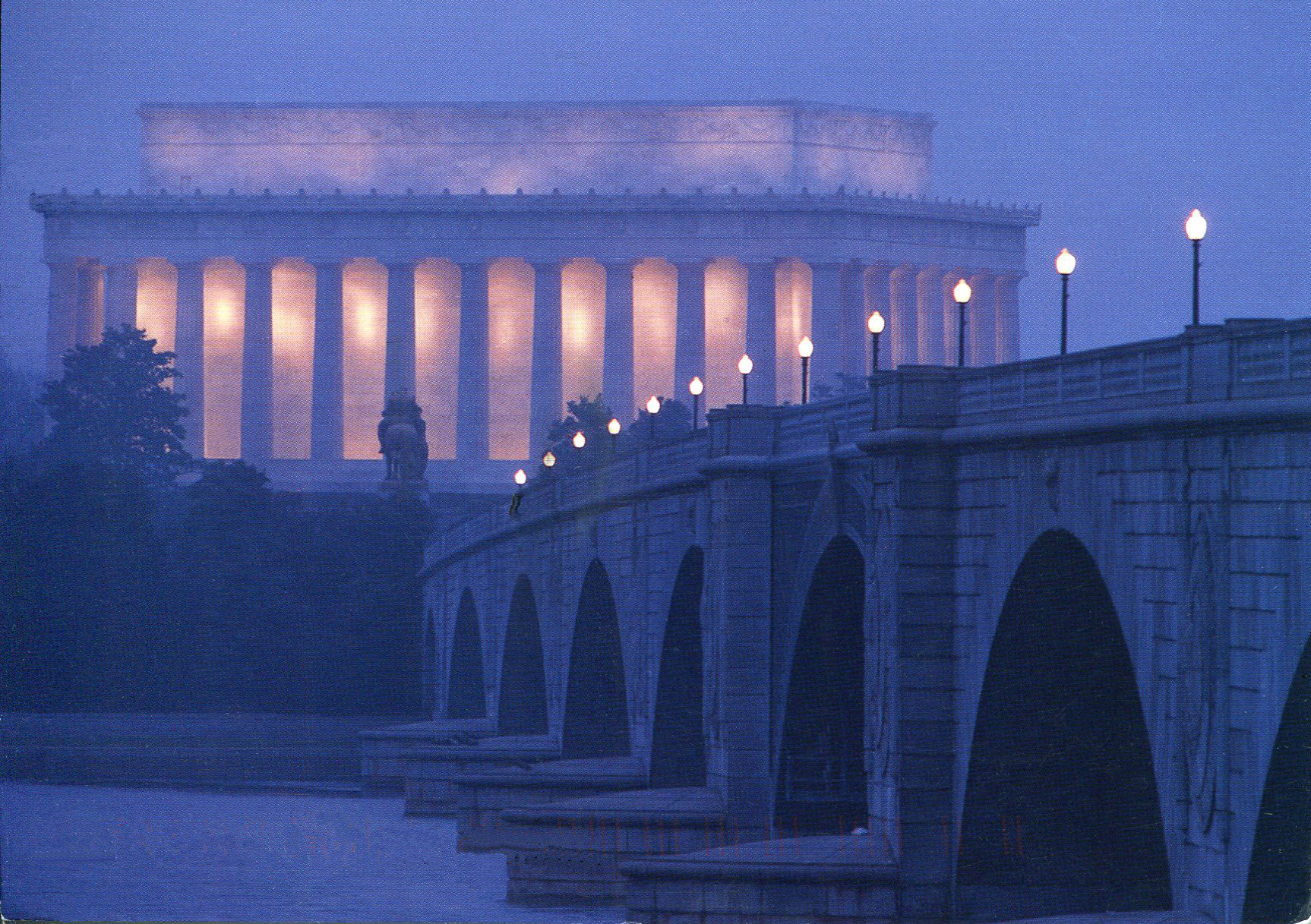 a lovely view of the lincoln memorial at twilight, seen beyond the bridge across the river. everything is soft and purple. the interior of the memorial is golden light. the lamps are lit on the bridge.
